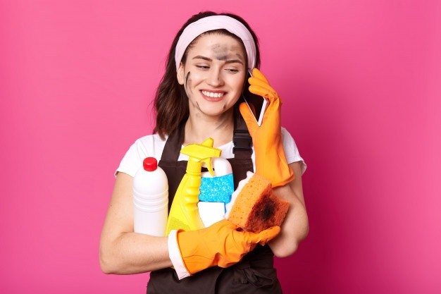 Positive caucasian woman speaking on mobile phone while clening her house, holding sponge and detergents in hands, dressed in casual clothes, wears rubber gloves and apron, isolated over pink wall. Premium Photo