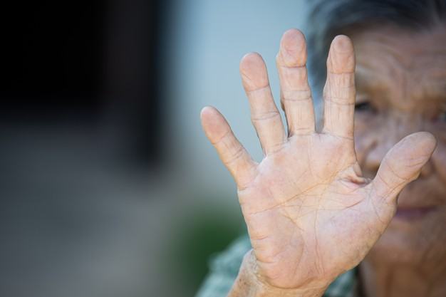 Close up picture of old woman's hand showing anti symbol Free Photo