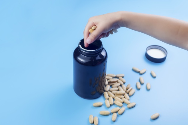 Close up view of child`s hands with pills, young child play alone with pills tablets at home. keep away from children reach concept. no medicine cabinet, raise awareness. Premium Photo