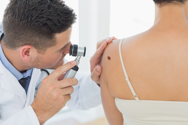 Doctor examining mole on back of woman Premium Photo