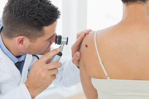 Doctor examining mole on back of woman Premium Photo
