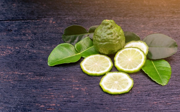Fresh bergamot fruit and green leaf on wooden table background. blank copy space Premium Photo