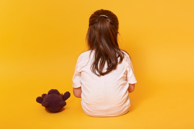 Little girl sitting backwards with brown teddy bear Free Photo