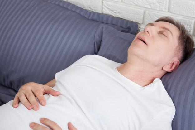 Man snoring because of sleep apnea lying in the bed. Premium Photo
