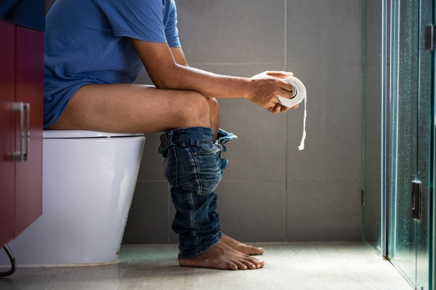 A man with a roll of a toilet paper in the toilet Premium Photo
