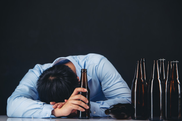 Alcoholic asian man with a lot of beer bottles Free Photo