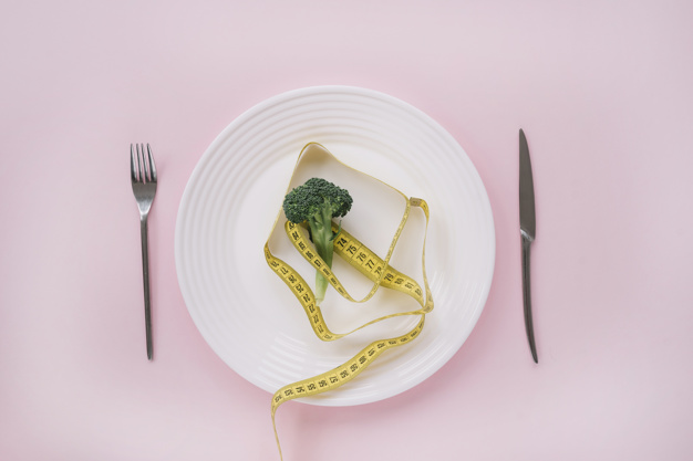 Broccoli and measurement tape on a dish Free Photo