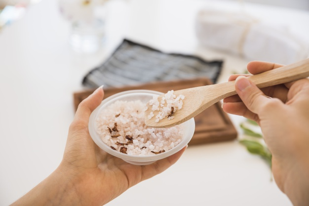 Faceless female with spoon and pink salt in bowl Free Photo