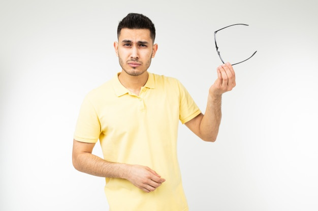 Guy feels pain in his eyes removing his glasses for vision on a white Premium Photo