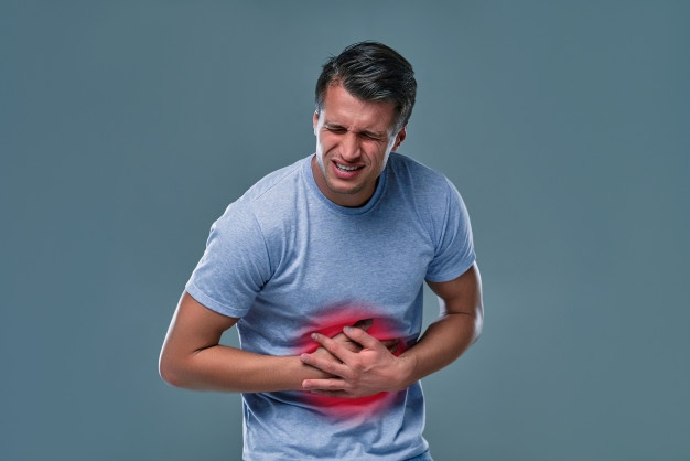 Man in white t-shirt with stomachache on gray room Premium Photo