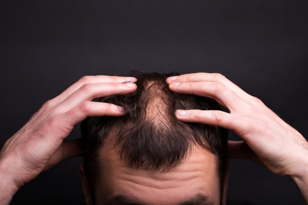 Men with bald head on a black wall close-up. Premium Photo