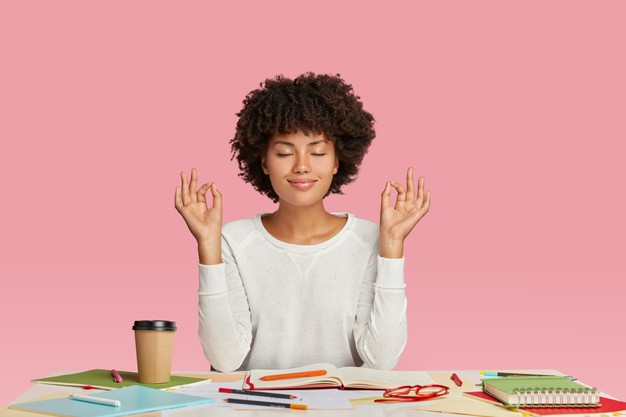 People, harmony and work concept. satisfied dark skinned woman with afro haircut, meditates at workspace, keeps eyes closed Free Photo