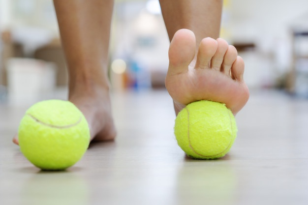 The tennis ball treatment : the ball will apply pressure to the painful spot and raise the procedure. Premium Photo