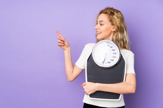 Young blonde woman isolated on purple wall with weighing machine and pointing side Premium Photo