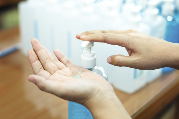 Woman cleaning hands with a hand sanitizer gel to prevent coronavirus contamination Free Photo