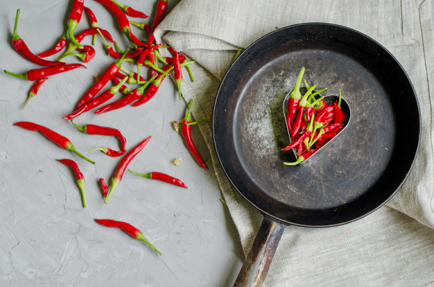 กินพริก พิชิตโรคLittle chilly peppers in a heart shape on an iron frying pan, concept of hot love and passion Premium Photo
