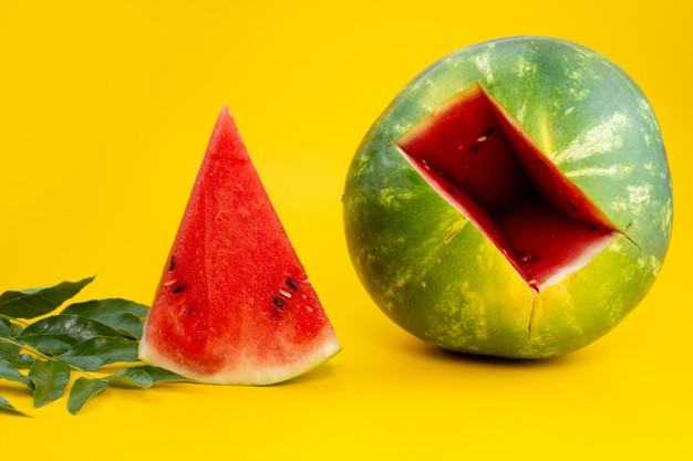 A watermelon next to a cut in half  Description automatically generated with low confidence